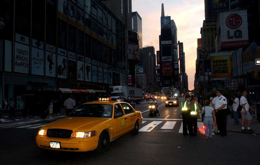 A taxi moves down Broadway through the heart of New York's Times Square at dawn on the day after a blackout that left U.S. and Canadian cities in the dark in this Aug. 15, 2003 photo.