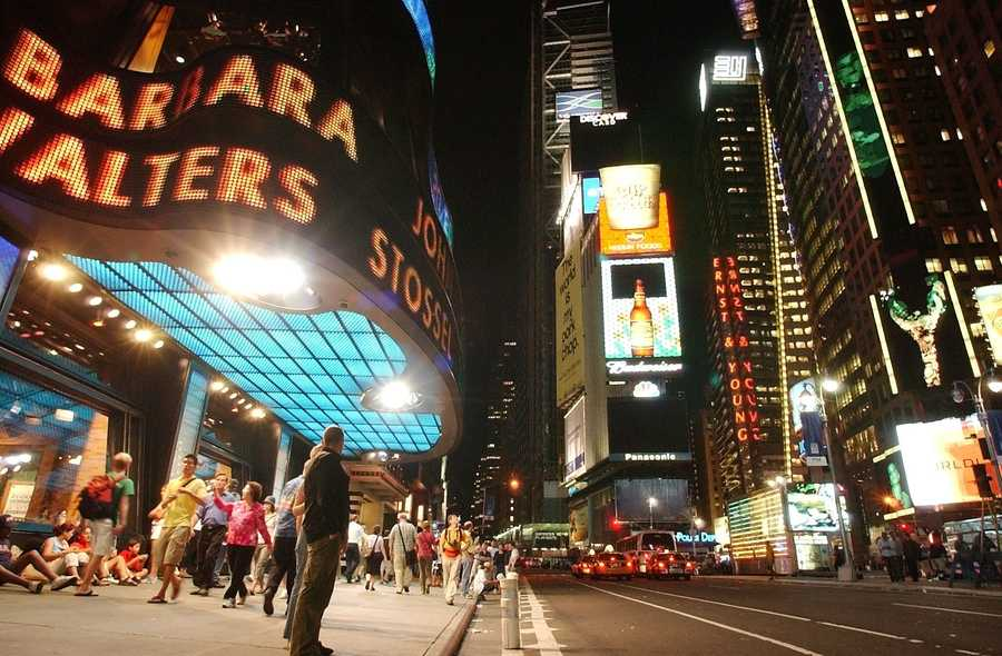 People walk under the bright lights of Times Square in New York, Friday, Aug. 15, 2003, after power returned to the city.