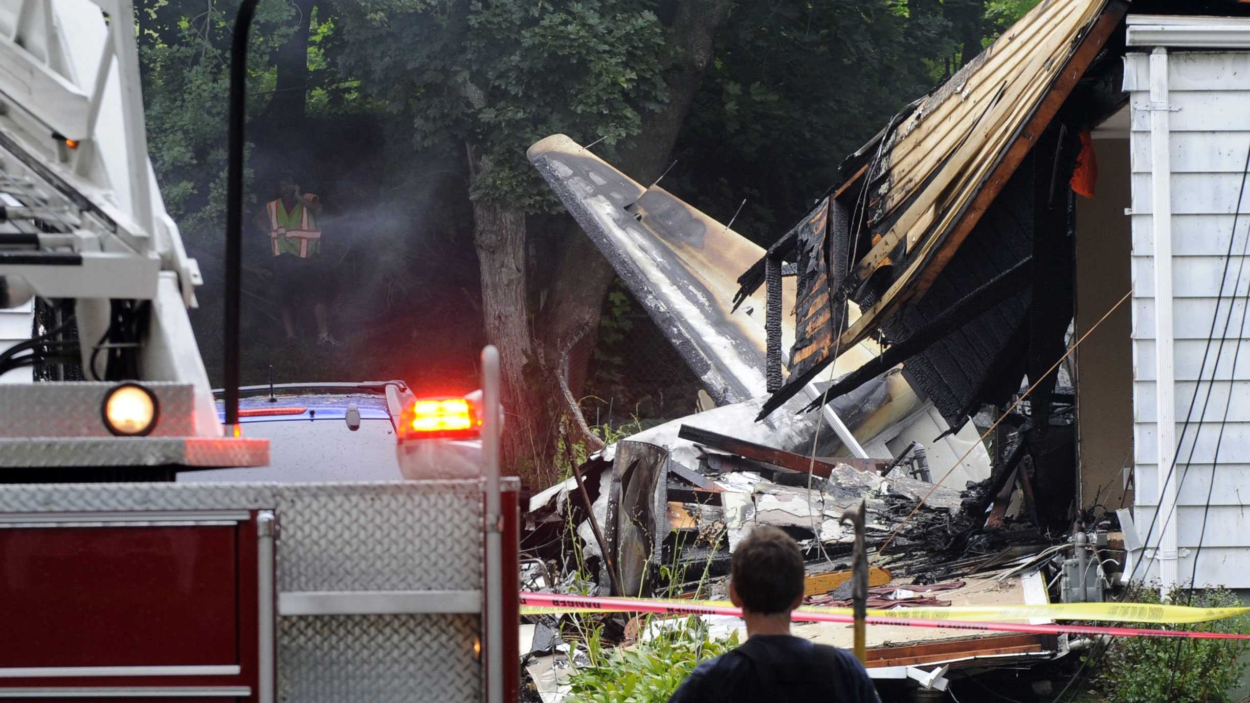 A firefighter surveys the scene of a small plane crash, Friday, Aug. 9, 2013, in East Haven, Conn. The multi-engine, propeller-driven plane plunged into a working-class suburban neighborhood near Tweed New Haven Airport, on Friday.
