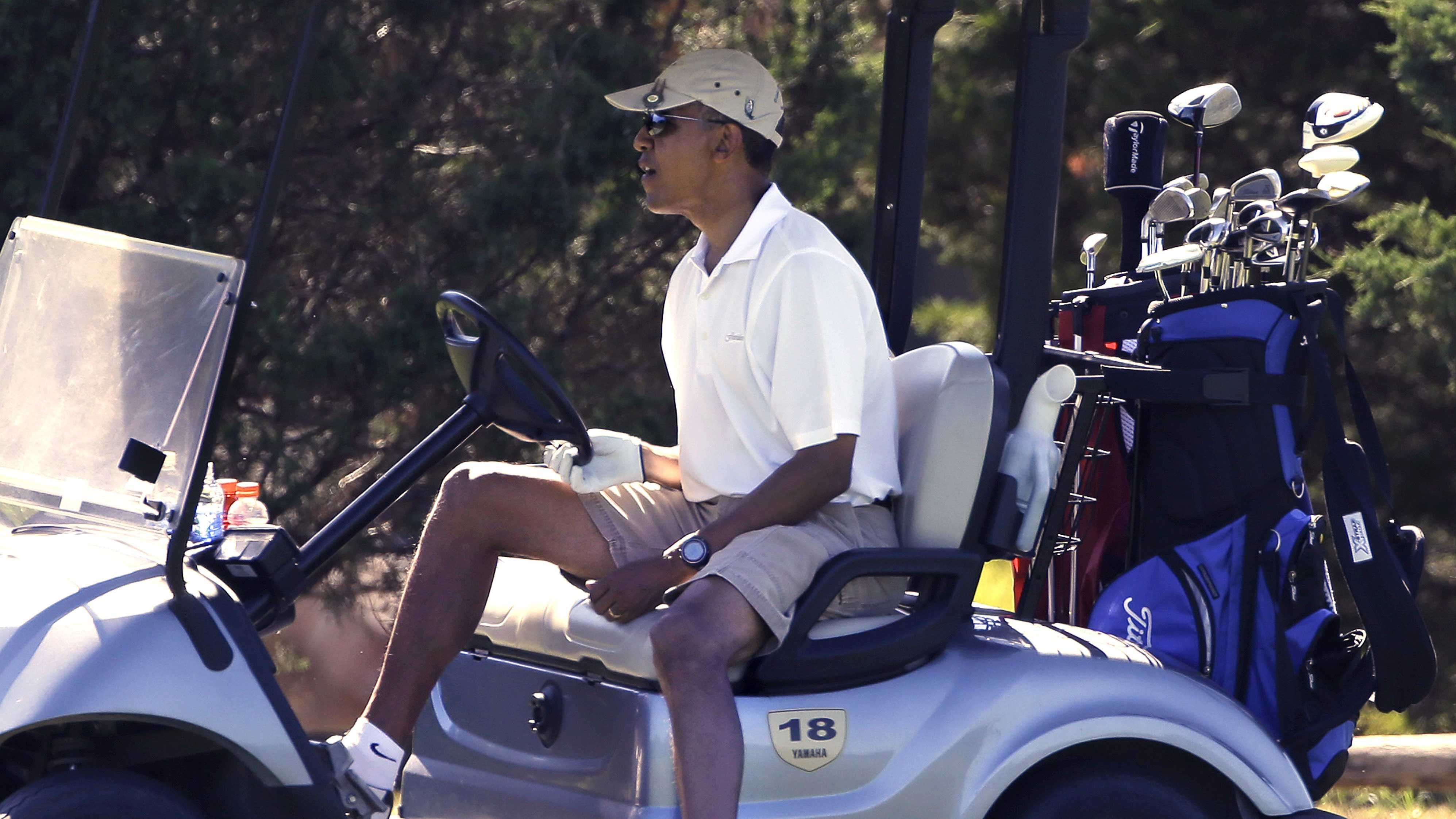 President Barack Obama steers his cart while golfing at Farm Neck Golf Club in Oak Bluffs, Mass., on the island of Martha's Vineyard Sunday, Aug. 11, 2013.