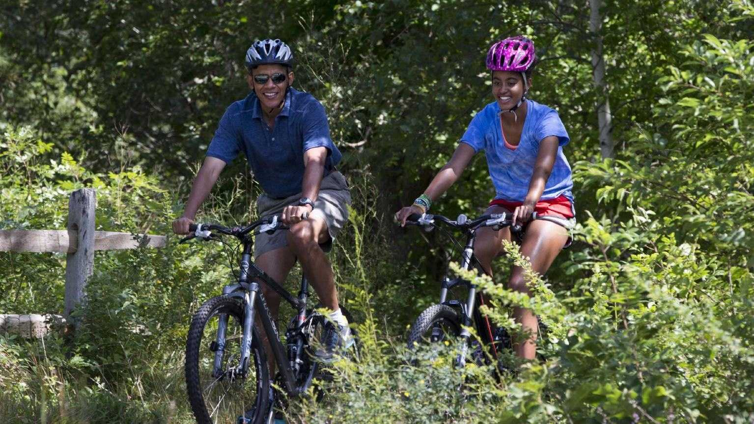 Malia Obama, right, followed by her father, President Barack Obama, ride their bikes in Manuel F. Correllus State Forest in West Tisbury, Mass., after first lady Michelle Obama, with daughter Sasha, passed by first, Friday, Aug. 16, 2013, during their family vacation on the island of Martha's Vineyard.