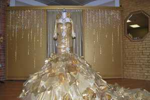 "They call Kayla's dress ""From Rags to Riches"" because they used hundreds of ""rags"" in the design. The design team tore up pieces of assorted gold fabrics&#x3B; gold lame, brocade and re-embroidered organza to create the textured wedding dress."