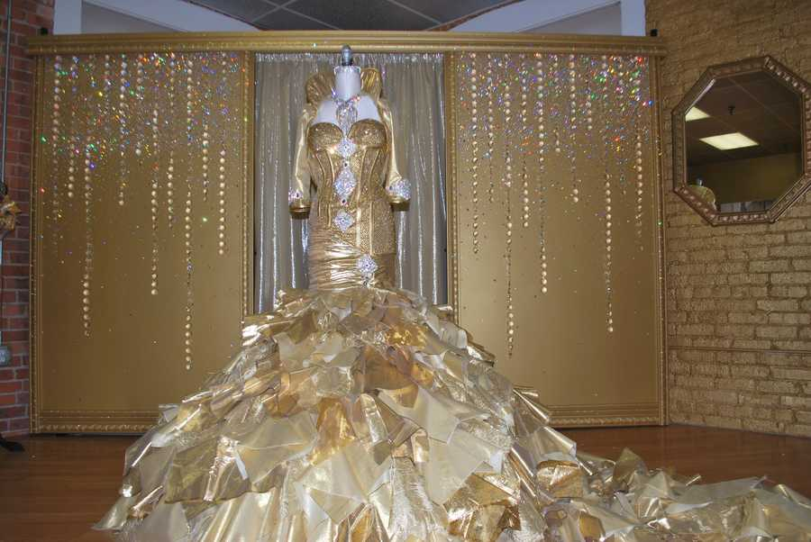 """They call Kayla's dress """"From Rags to Riches"""" because they used hundreds of """"rags"""" in the design. The design team tore up pieces of assorted gold fabrics&#x3B; gold lame, brocade and re-embroidered organza to create the textured wedding dress."""