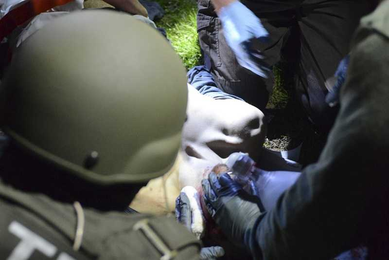 Massachusetts State Police photo, tactical emergency medical technicians tend to Boston Marathon bombing suspect Dzhokhar Tsarnaev at the time of his capture by law enforcement authorities in Watertown, Mass.(Photos of the Boston Marathon bombing suspect's surrender have been posted on the Boston Magazine website. The additional images, made public made public Tuesday, Aug. 27, 2013, were among those released to the magazine last month by a state police photographer.)