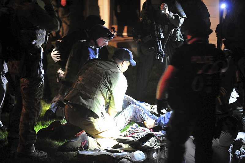 Massachusetts State Police photo, tactical emergency medical technicians tend to Boston Marathon bombing suspect Dzhokhar Tsarnaev, partially obscured center, at the time of his capture by law enforcement authorities in Watertown, Mass.Photos of the Boston Marathon bombing suspect's surrender have been posted on the Boston Magazine website. The additional images, made public Tuesday, Aug. 27, 2013 were among those released to the magazine last month by a state police photographer.
