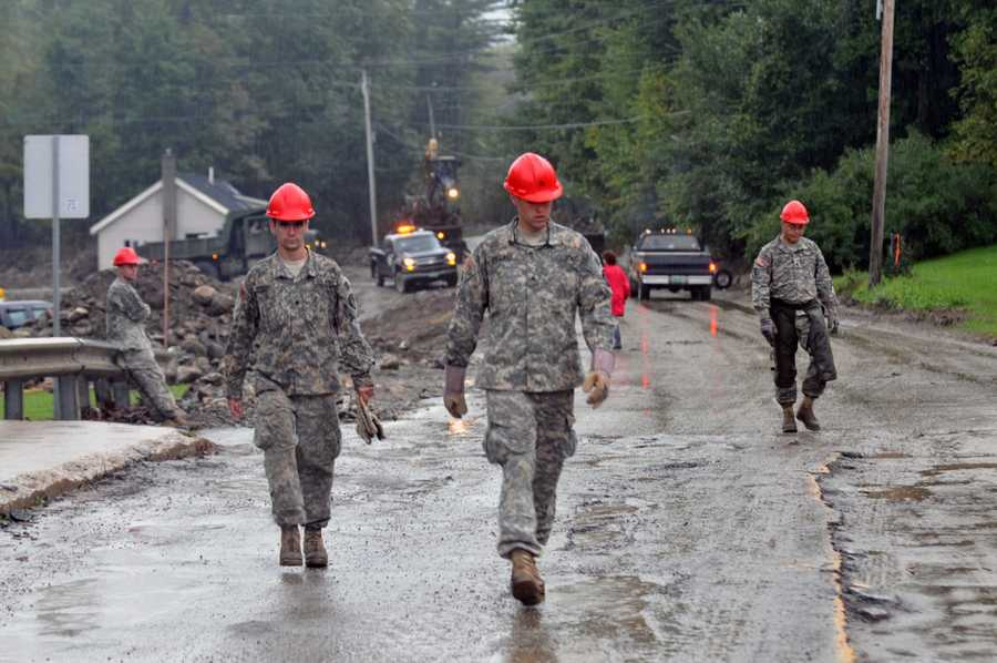Members of the Maine National Guard take a break after working into the evening to fix damage caused by Hurricane Irene in Pittsfield, Vt.