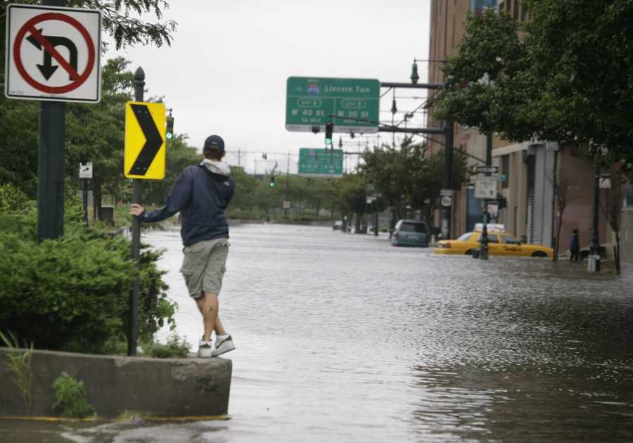 A man surveys the floodwaters on Manhattan's West Side after Hurricane Irene, downgraded to a tropical storm, hit New York. A year later, the city would receive a much harder hit from Hurricane Sandy.