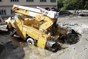 A truck lies in a hole created by the raging waters created by Tropical Storm Irene on Monday, Aug. 29, 2011 in Berlin, Vt.