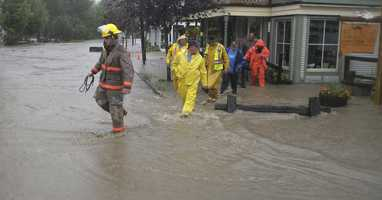 Waitsfield firefighters and rescuers wade through a street flooded by rain from Tropical Storm Irene after assisting residents in a building in Waitsfield, Vt., Sunday, Aug. 28, 2011.