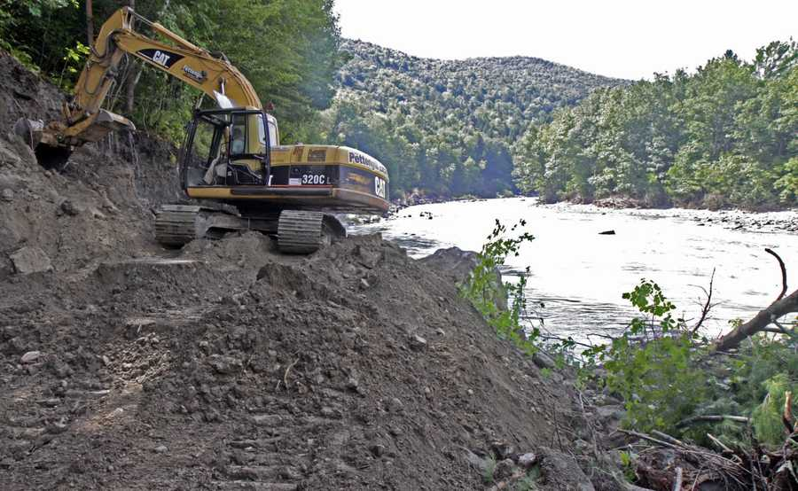 An excavator works on rebuilding Vermont Route 107 next to the White River in Bethel, Vt. Huge sections of the road were washed completely away.