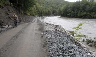A bicyclist rides along the single lane of Vermont Route 107 washed out by floodwaters of the White River in Bethel, Vt.