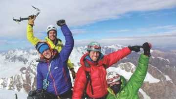 Westford native Rob Gleich, at left in rear, celebrates with, from left, Austin Lines, Zach Matthay and Jeffrey Longcor, at the top of a Himalayan peak in Kyrgyzstan on July 23.