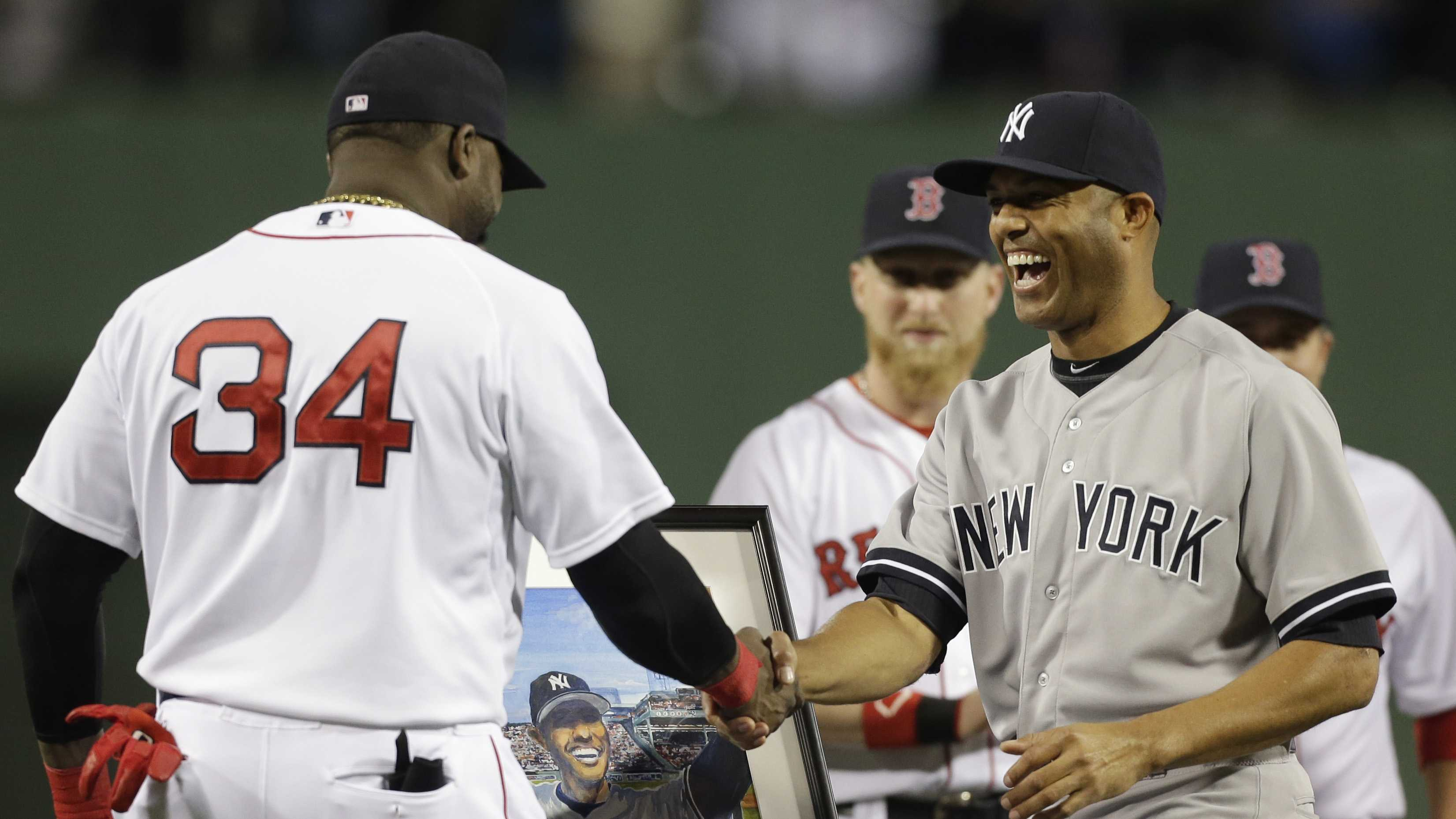 New York Yankees relief pitcher Mariano Rivera, right, shakes hands with Boston Red Sox's David Ortiz, left, as Ortiz presents him with a portrait, behind, during a tribute to Rivera before the start of a baseball game at Fenway Park, Sept. 15, 2013.