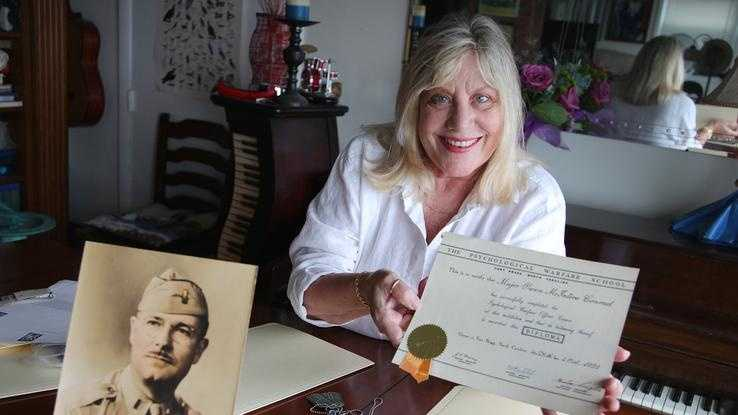 Deborah Campbell of Quincy, who discovered her late grandfather, Owen Conrad, was a spy in the U.S. World War II intelligence agency the OSS and in its successor organization, the CIA, shows off a commemoration he received.
