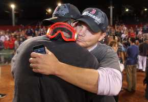 Boston Red Sox general manager Ben Cherington, right, is embraced by a player after the Red Sox clinched the AL East title with a 6-3 win over the Toronto Blue Jays in a baseball game at Fenway Park, Friday, Sept. 20, 2013, in Boston.