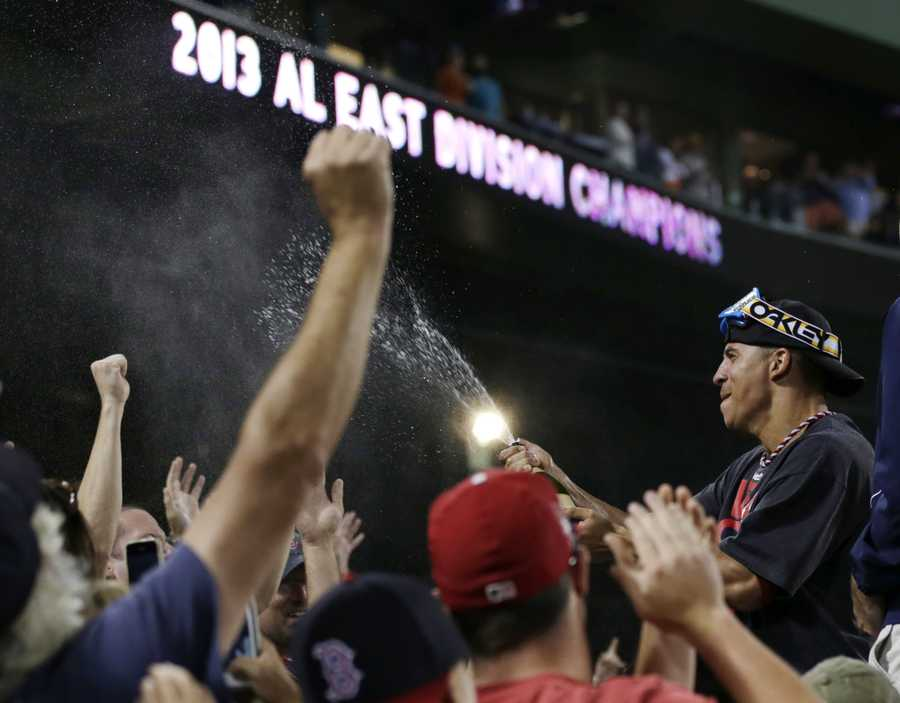 Boston Red Sox's Quintin Berry sprays fans with sparkling wine after the Red Sox clinched the AL East title with a 6-3 win over the Toronto Blue Jays in a baseball game at Fenway Park, Friday, Sept. 20, 2013, in Boston.