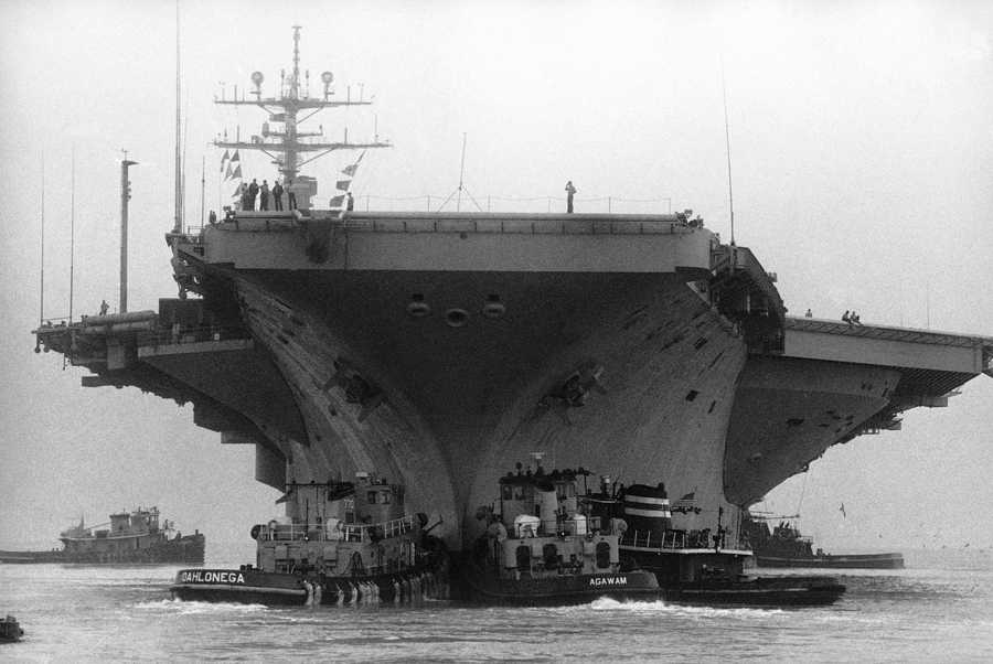 The aircraft carrier U.S.S. Eisenhower leaves the Norfolk Naval Base on Thursday, Sept. 26, 1985, under the eyes of Marines. The huge carrier was ordered to sea as Hurricane Gloria approached the eastern coastline.