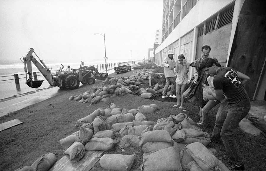 Volunteers sandbag the front of a boarded up ocean front hotel on Thursday, Sept. 26, 1985 in Virginia Beach, Virginia, as Hurricane Gloria moves closer. The huge storm, packing 130 m.p.h., winds, is expected to make landfall late Thursday at night or early Friday in morning.