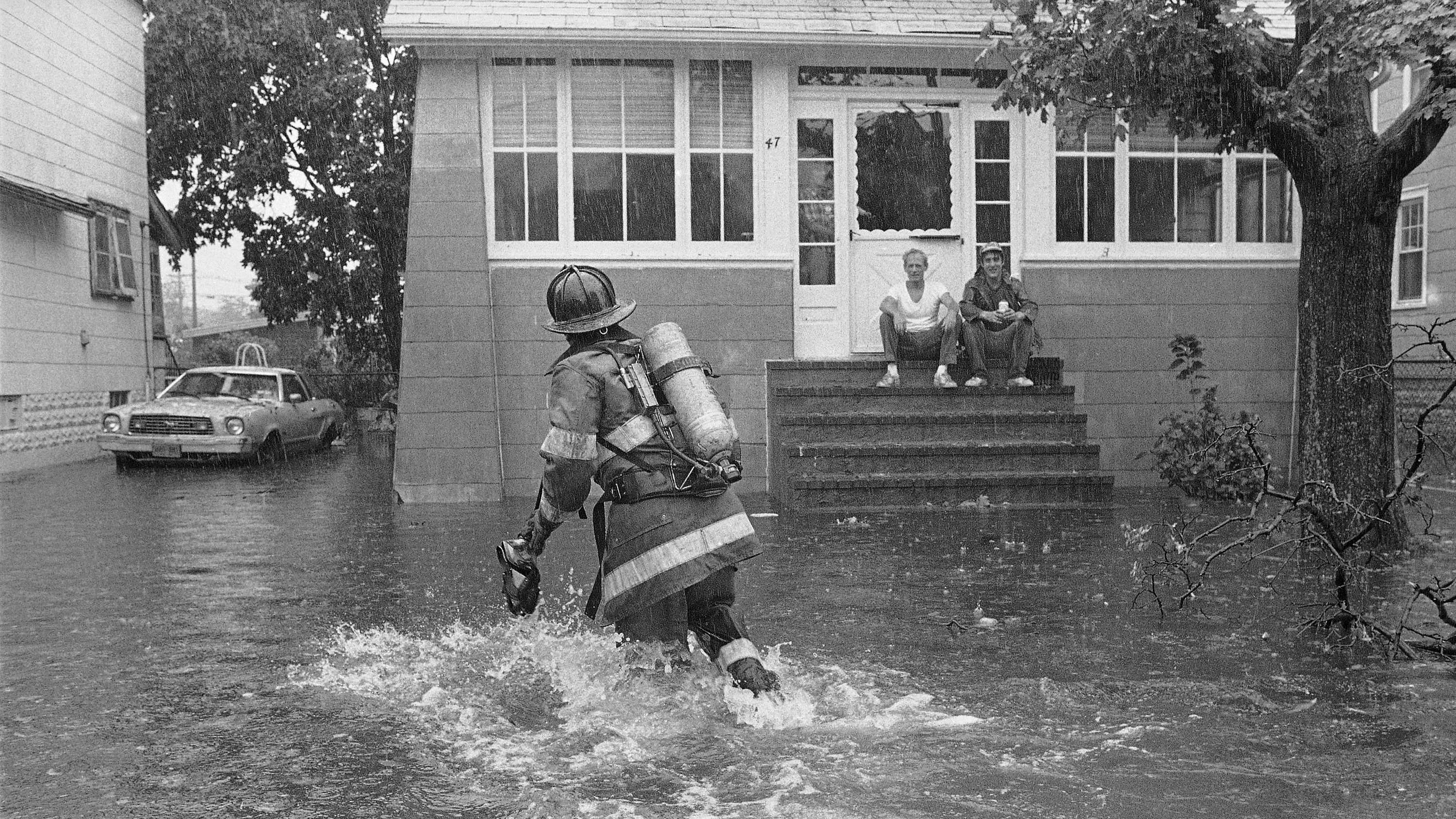 A firefighter makes his way through knee-deep water as he checks flooding conditions on Gordon Place in Freeport, New York, Sept. 27, 1985. Howling winds and heavy rain from Hurricane Gloria flooded local streets as the storm passed over the Long Island community.