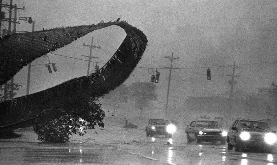 Motorists on Long Beach Ave., in Oceanside, N.Y., pass an unusual obstacle as howling winds from hurricane Gloria blow a chain link fence in the air on Friday, Sept. 27, 1985. Heavy rain and winds from the hurricane passed over the Long Island community on Friday in Morning.