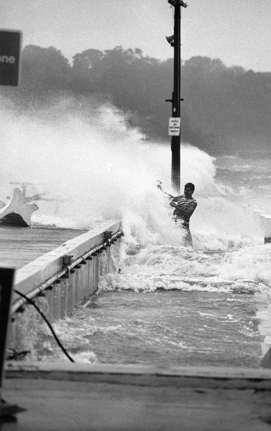 An unidentified man is hit by a wave as he walked on the side of a pier in New London, Connecticut on Friday, Sept. 28, 1985, during the height of Hurricane Gloria. The hurricane swept into Connecticut with winds of 90 miles per hour, but damage was said to be minimal.