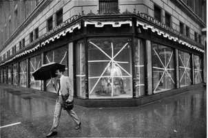 An unidentified man carries an umbrella as he walks in the rain past Saks Fifth Avenue in New York City, Friday morning September 27, 1985. The windows of Saks have been taped up as the city braces for the arrival of Hurricane Gloria.