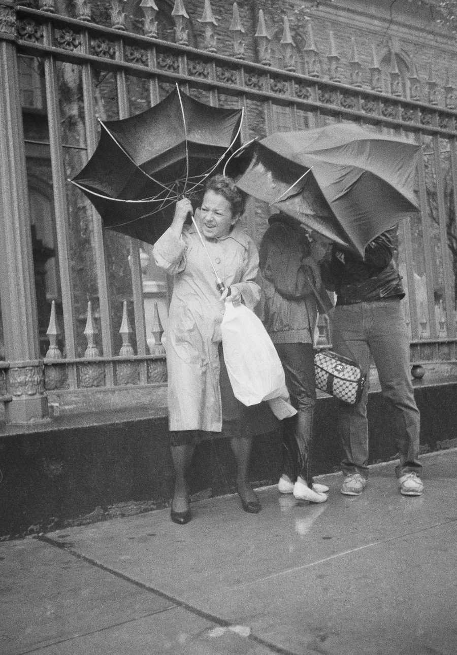 Three unidentified New Yorkers brace themselves against Hurricane Gloria in downtown Manhattan, Sept. 27, 1985, New York. Driving rains and high winds battered commuters as they made their way to work in the city.