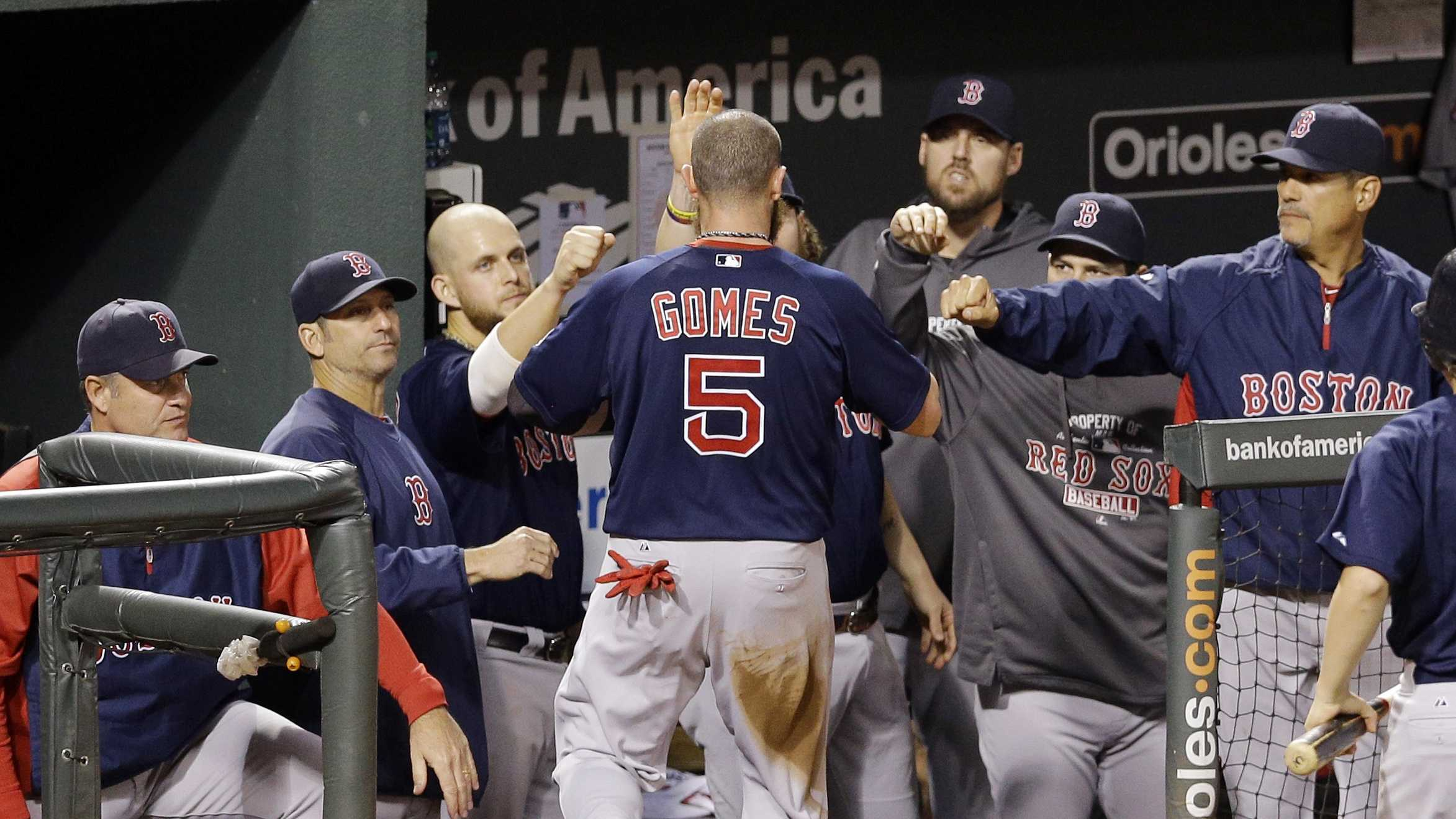 Boston Red Sox Jonny Gomes is greeted by teammates in the dugout after scoring on a single by David Ross in the fourth inning of a baseball game against the Baltimore Orioles, Sept. 28, 2013, in Baltimore.