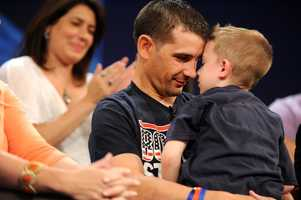"""Marc Fucarile and son, Gavin. Behind them sits Celeste Corcoran, 47, who lost both legs below the knee in the bombings. """"I do not want to die. I've got so much to do,"""" Corcoran thought in the moments after bombing. """"I've got my kids. I have my life. I have my husband."""""""