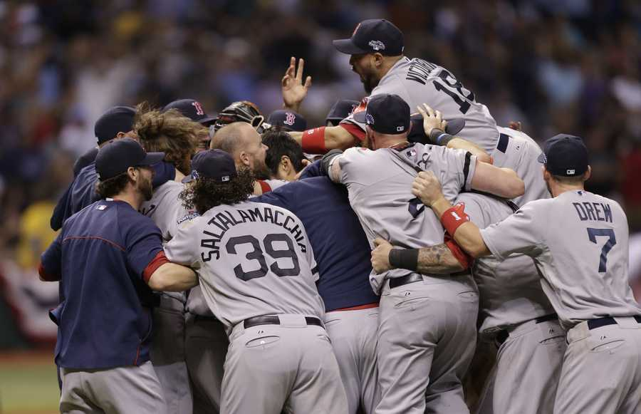 The Boston Red Sox's celebrate on the field after defeating the Tampa Bay Rays in Game 4 of an American League baseball division series, Wednesday, Oct. 9, 2013, in St. Petersburg, Fla.
