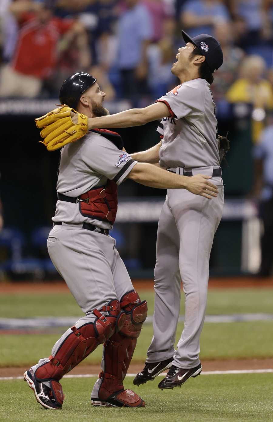Boston Red Sox pitcher Koji Uehara, right, jumps on catcher Jarrod Saltalamacchia, after the team defeated the Tampa Bay Rays.