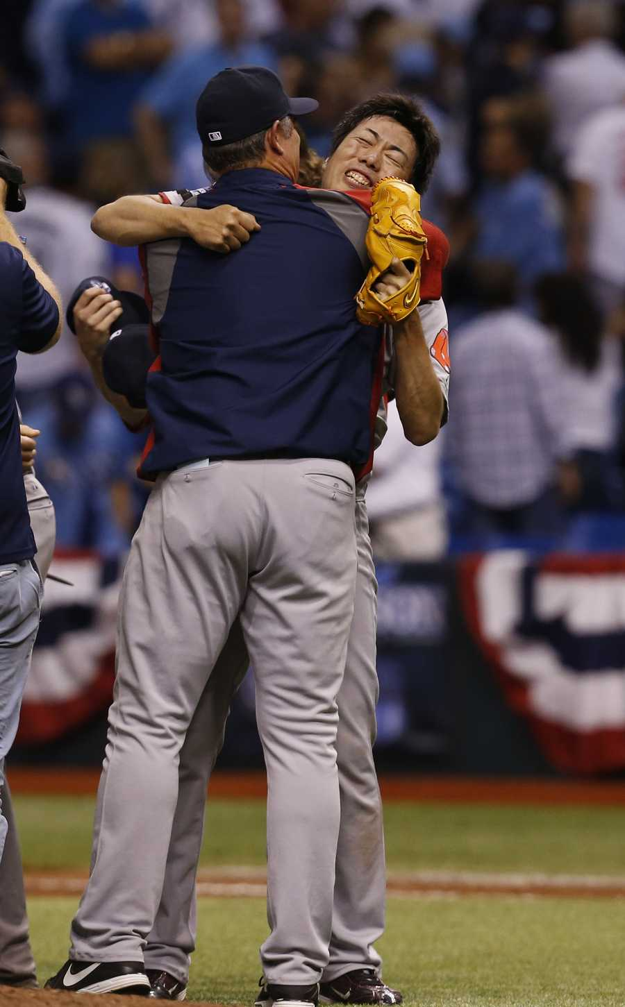 Boston Red Sox relief pitcher Koji Uehara is hugged by manager John Farrell.