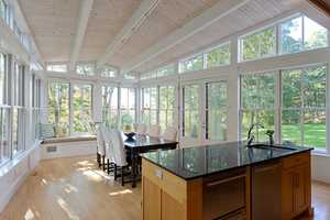 The spacious kitchen has custom finishes and a bright dining area surrounded by walls of windows.