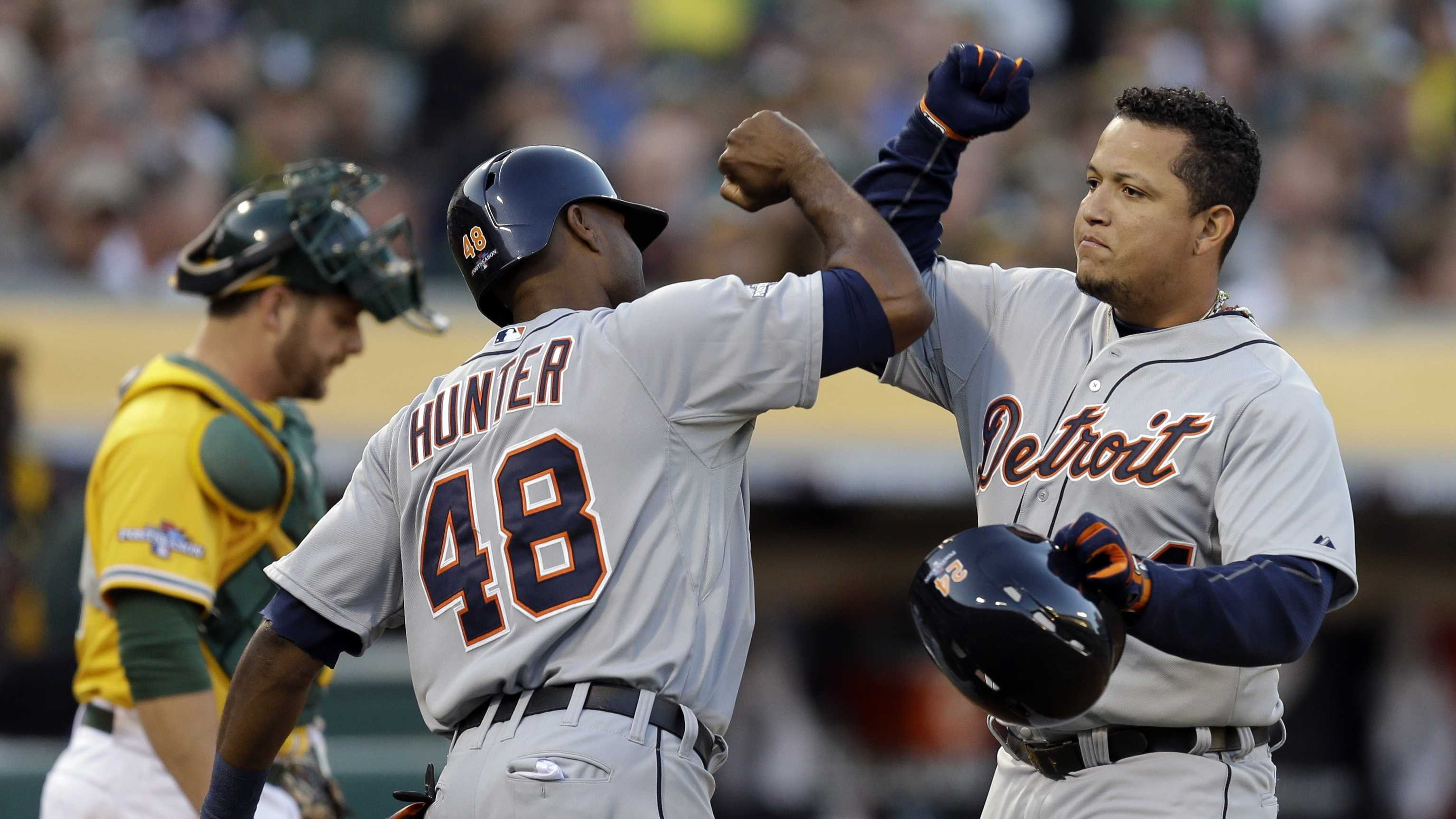 Detroit Tigers Miguel Cabrera (24) celebrates with teammate Torii Hunter (48) after he scored a two run home run that also scored Hunter in the fourth inning of Game 5 of an American League baseball division series against the Oakland Athletics in Oakland, Calif., Thursday, Oct. 10, 2013.