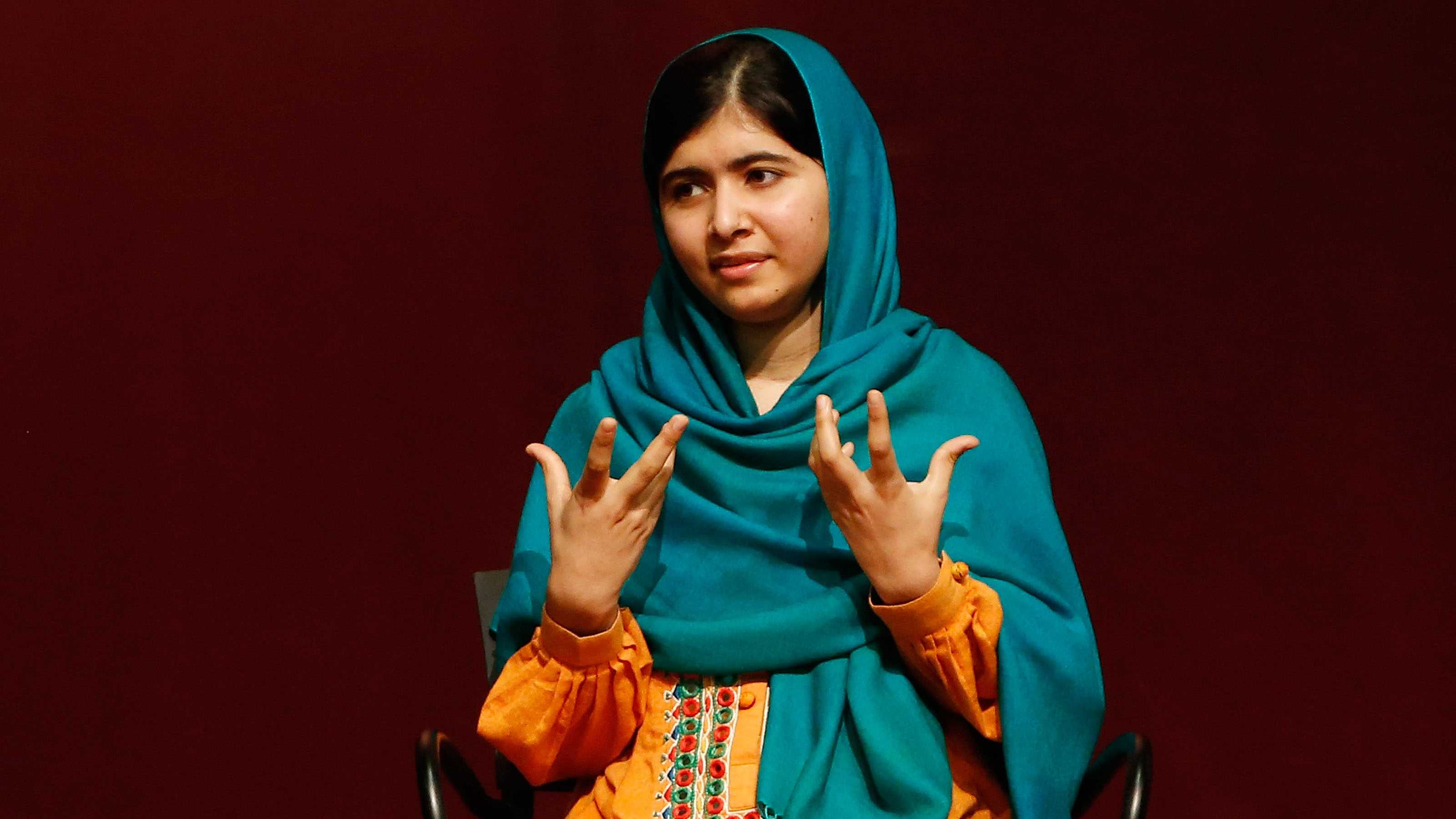 "Malala Yousafzai gestures as she speaks to an audience during a discussion of her book, ""I am Malala"" hosted by the John F. Kennedy Library and held at Boston College High School Saturday, Oct. 12, 2013, in Dorchester, Mass."