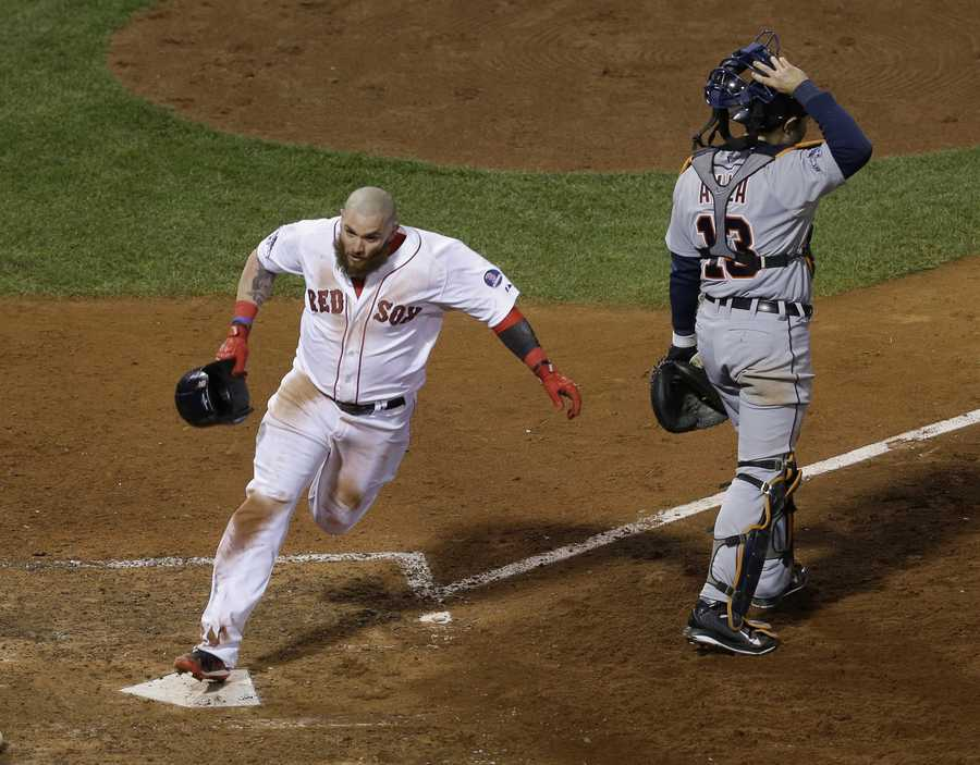 Boston Red Sox's Jonny Gomes scores the winning run on a hit by Jarrod Saltalamacchia during Game 2 of the American League baseball championship series against the Detroit Tigers Sunday, Oct. 13, 2013, in Boston. At right is Detroit Tigers' Alex Avila. The Red Sox won 6-5.