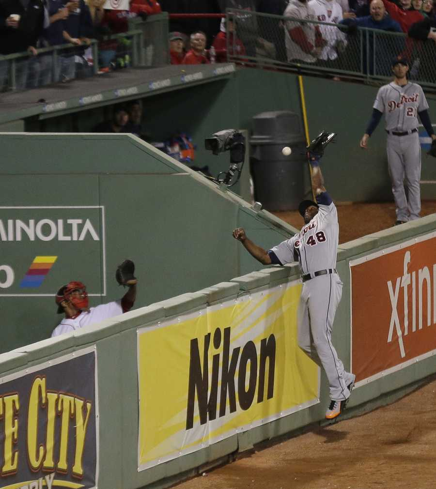 Detroit outfielder Torii Hunter leaps for the ball as it clears the bullpen fence.