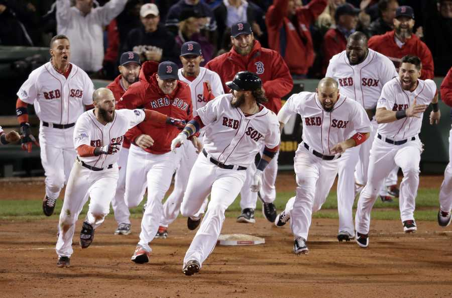 Boston Red Sox players run after Jarrod Saltalamacchia after Saltalamacchia hits the game winning single during Game 2 of the American League baseball championship series against the Detroit Tigers Sunday, Oct. 13, 2013, in Boston. The Red Sox won 6-5.