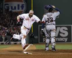 Boston Red Sox's Jonny Gomes scores the winning run on a hit by Jarrod Saltalamacchia during Game 2 of the American League baseball championship series against the Detroit Tigers Sunday, Oct. 13, 2013, in Boston. At right is Detroit Tigers' Alex Avila.