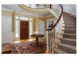The entrance features a grand two story foyer with bridal staircase.