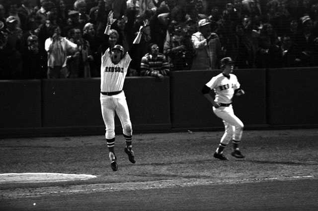 """""""Church bells rang throughout New England""""Carlton Fisk jumps as he sees his 12th-inning home run hit the left field foul pole to win the sixth game of the World Series against Cincinnati, October 22, 1975."""
