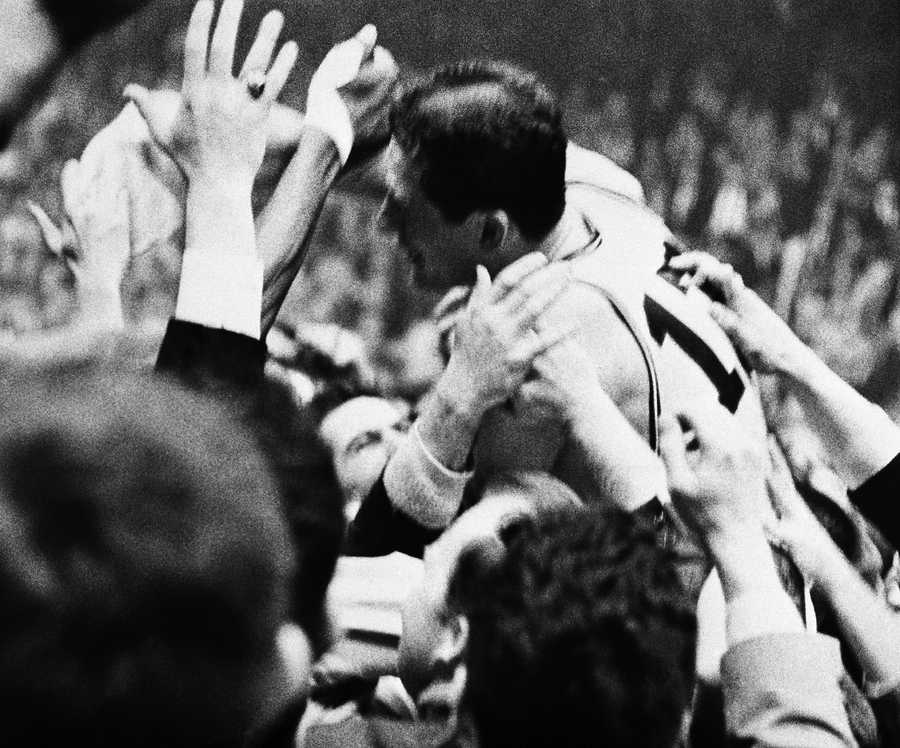"""""""Havlicek Stole the Ball"""" John Havlicek of the Boston Celtics is mobbed by fans and placed on their shoulders after the Celtics defeated the Philadelphia 76'ers 110 to 109 to win the Eastern Division Championship of the National Basketball Assn. at Boston Garden, April 16, 1965. Havlicek intercepted a Philadelphia throw-in pass in the last seconds of the game."""