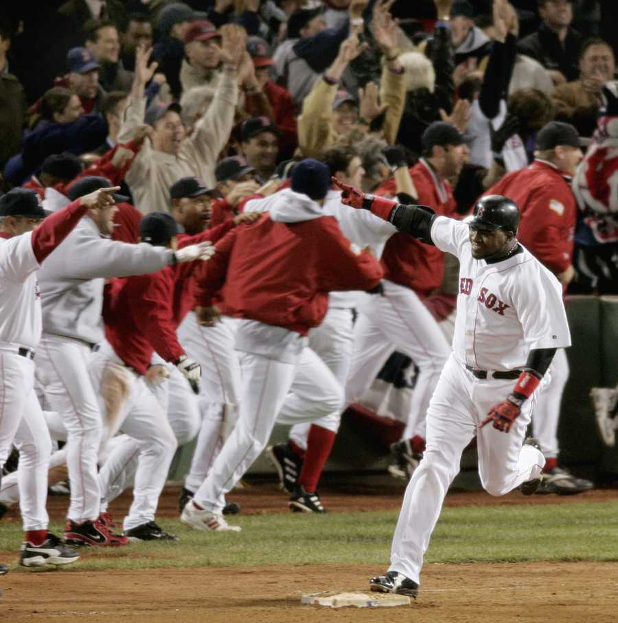 """""""Papi's walk-off home run""""David Ortiz celebrates as he rounds first base after hitting a game-winning home run in the 12th inning against the New York Yankees, of Game 4 of the AL championship series Oct. 17, 2004, at Boston's Fenway Park."""