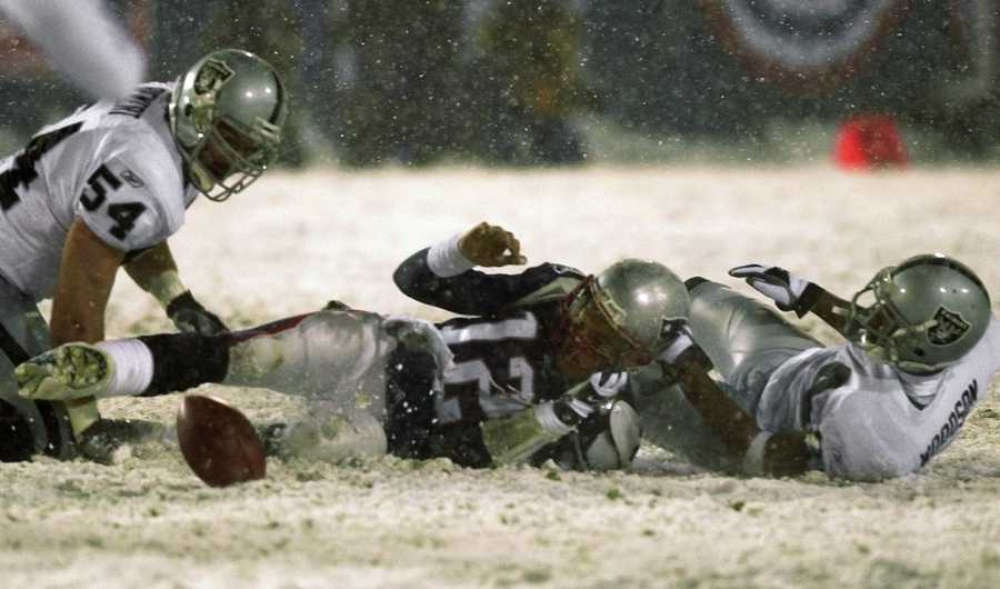"""""""The Tuck Rule or Snow Bowl""""Tom Brady loses the ball after being brought down by Oakland Raiders' Charles Woodson, right, while Greg Biekert (54) moves to recover the ball in the fourth quarter of their AFC Division Playoff game in Foxborough, Jan. 19, 2002. The Patriots retained possession after officials ruled that Brady's arm was moving forward, making it an incomplete pass. The Patriots went on to win, 16-13, in overtime."""
