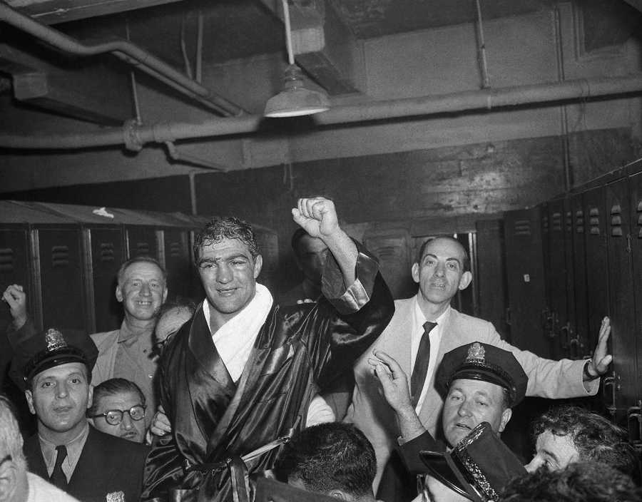 """""""The Real Rocky""""Brockton's Rocky Marciano raises his hand to acknowledge cheers in his dressing room after he was crowned new heavyweight champion with a 13th-round knockout of Jersey Joe Walcott in Municipal Stadium in Philadelphia, Sept. 23, 1952."""