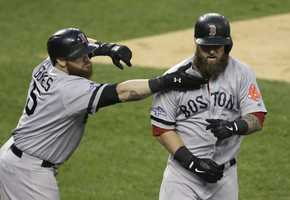 Boston Red Sox's Jonny Gomes reaches to pull the beard of Mike Napoli after Napoli hits a home run in the seventh inning during Game 3 of the American League baseball championship series against the Detroit Tigers Tuesday, Oct. 15, 2013, in Detroit.