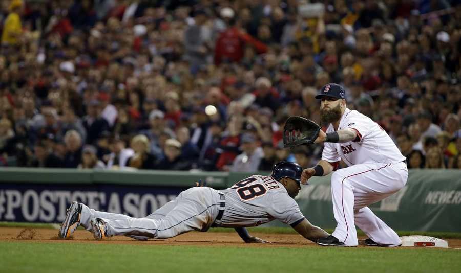 Detroit Tigers' Torii Hunter dives back into first base in front of Boston Red Sox's Mike Napoli on a pick-off attempt by Red Sox starting pitcher Clay Buchholz.