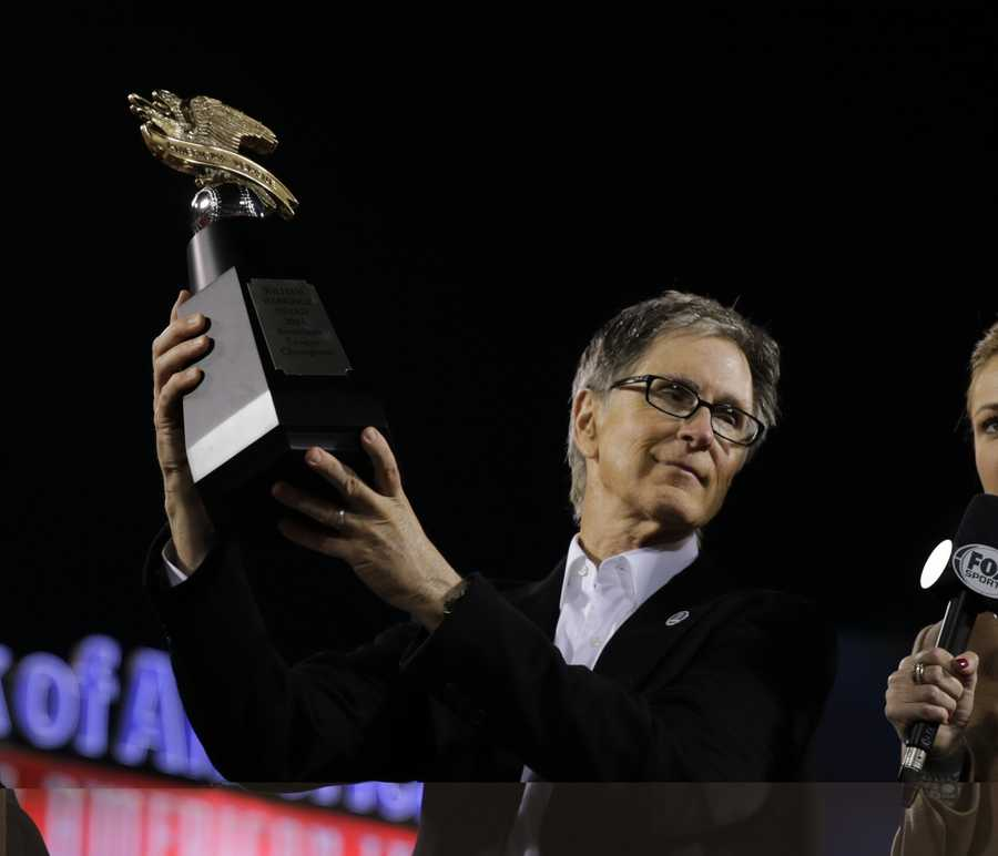 Boston Red Sox owner John Henry hoists the championship trophy after the Red Sox beat the Detroit Tigers 5-2 in Game 6 of the American League baseball championship series on Saturday, Oct. 19, 2013, in Boston. The Red Sox advance to the World Series.