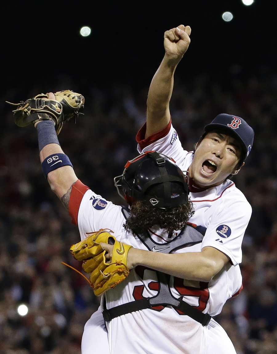 Boston Red Sox relief pitcher Koji Uehara, rear, and catcher Jarrod Saltalamacchia celebrate the Red Sox 5-2 win over the Detroit Tigers in Game 6 of the American League baseball championship series on Saturday, Oct. 19, 2013, in Boston. The Red Sox advance to the World Series.