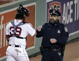 Boston Red Sox catcher Jarrod Saltalamacchia (39) gives a fist bump to Boston police officer Steve Horgan before Game 6 of the American League baseball championship series between the Boston Red Sox and the Detroit Tigers on Saturday, Oct. 19, 2013, in Boston. Horgan gained notoriety when he raised his arms in jubilation after the Red Sox's David Ortiz hit an eighth-inning grand slam during Sunday's Game 2 in Boston.